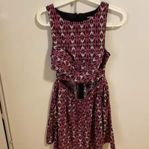 En mönstring klänning med fickor och fin öppning vid magen bara framifrån. Oanvänd