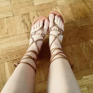 """🌻Flätade """"gladiator""""-sandaler med guldiga smycken/applikationer och tofsar i ändarna. Sparsamt använda. Vid frakt tillkommer 50 kr 🌻"""