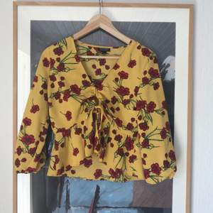 Söt blus som blir perfekt i sommar! Färgen är rättvist visad på andra bilden. Knäpps med en knapp och knyts framtill.  Möts ej upp, skickar endast, men frakten ingår i priset!