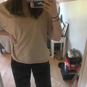 En beige t-shirt med rosa sömmar. En ficka. Använd få gånger. Passar dig med storleken sx/s. OBS: har råkat spilla tre små klorinfläckar längst ned i kanten, syns inte mycket men brukar stoppa in den i fram😊