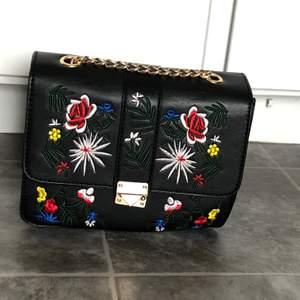 en gullig väska med broderade blommor och guldkedja:) har en liten ficka där i ock är endast använd ett fåtal gånger! passar perfekt till en mer basic outfit 🥰