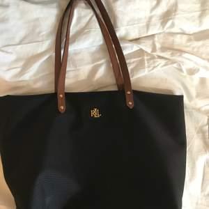 En svart handväska från Ralph Lauren med bruna band och guldiga detaljer. Beige inuti med ett litet avtagbart fack för ex. telefon/kort. (Bild kan skickas vid intresse). Den är använd men fortfarande i bra skick. Mått ca: 44x28 cm⭐️. (Pris är exkl. frakt)