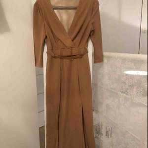 En långklänning med slits på sidorna, meshad rygg. Använd en gång. Ett fint bälte med metallplåt ingår också som ger en röda mattan känsla och ger en fin siluett 💛