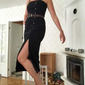 Snygg, svart jeansklänning med slits vid benen. Från Asos. Helt oanvänd så väldigt bra skick! Stängs med dragkedja baktill. Justerbara band. Storlek 40 men sitter lika bra på mig som har 38. (Skärpet ingår ej) Nypris i butik: ca 500kr. Frakt: 49kr