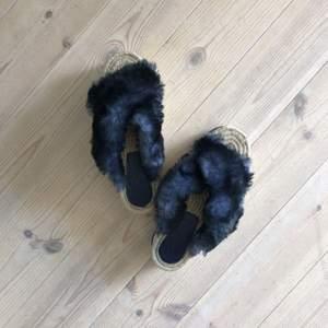Platform-sandaler med mörkblå fuskpäls. Gummisula och bast.
