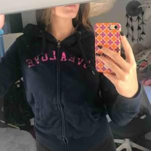 Marinblå luvtröja med rosa text ifrån Svea. KÖPARE STÅR FÖR FRAKT