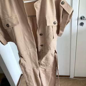 Beige jumpsuit från HM i storlek 36! Använd fåtal gånger. Har ett bälte i midjan och knappar samt blixtlås framtill 😍 100kr