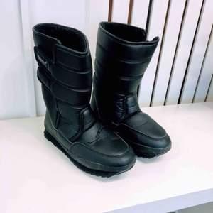 Höga vinterskor med halkskydd, utfällbar metallplatta med piggar under skon. Använda en gång. (Swish-betalning: Finns i Rissne/köparen står för frakten.)