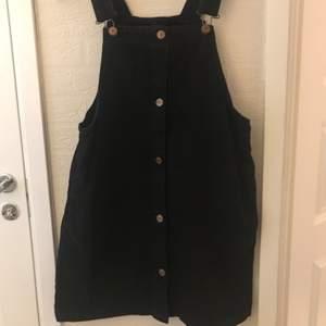 Svart klänning med spännen och fickor i strl S från MONKI
