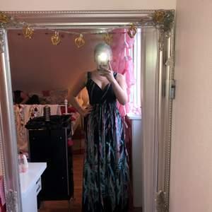 Jag säljer en lång svart klänning med lite rosa och blåa i. Jag är 165cm lång. (priset kan diskuteras)