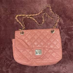 En vintage rosa mini väska från 2000-talet. Silver kedja med rosa tyg remsor, 2 fack och ett litet fack. Rosa insida. Från Gina Tricot. Färg har lossnat från rosa banden, annars i Bra skick! ✨ OBS! Rosa remsorna i kedjebandet tappar fortfarande färg. Gammalt material!