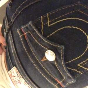 """ett par superfina mörkblåa lågmidjade true religon jeans som är super sköna och stretchiga, skulle säga att dom är raka i benen alltså inte utsvängda och inte tajta med åt raka hållet, dom är slittade ner till av säljaren sen innan men går att sy upp då dom är ganska långa och då syr man bort slitten, dom är i storlek 25 så alltså en xs/s jag är i mellan xs/s och dom passar mig utmärkt🥺💞💞vid fler intresserade så blir det budgivning med 10kr i mellan varje bud❤️ """"högsta bud 120kr"""""""