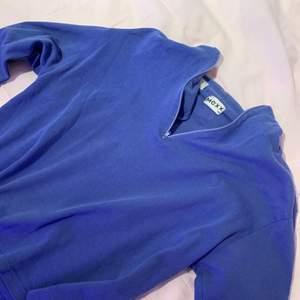 Blå/lila tröja med dragkedja upptill.