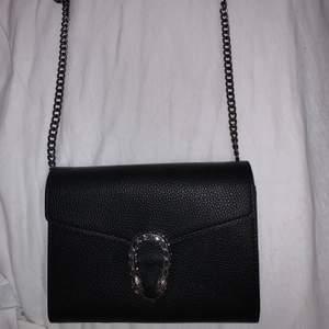 Svart handväska med lång silverkedja och en väldigt fin detalj. Har aldrig användt den så den är så gott som ny! Köparen står för frakten men kan även mötas upp☺️ hör av er om ni vill ha fler bilder på den!