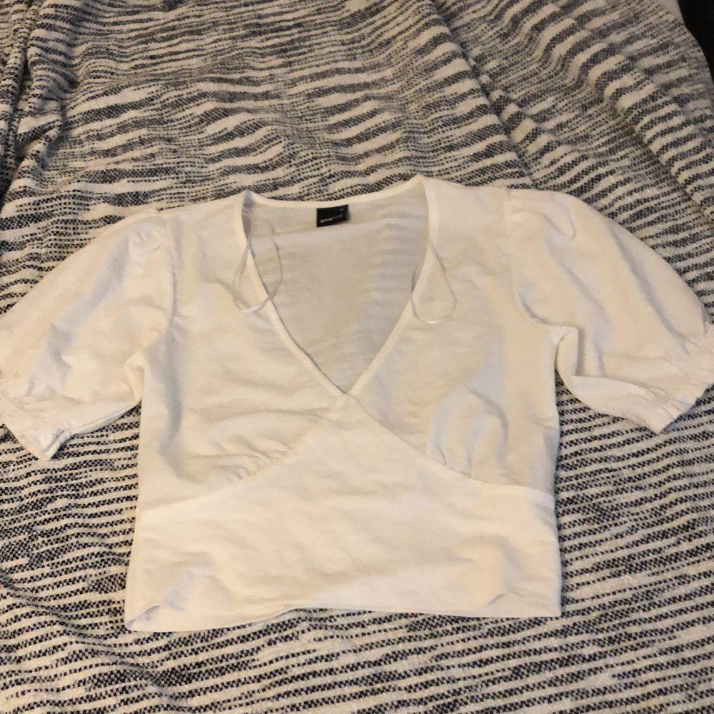 En kort vit tröja från Gina men som tyvärr var för liten för mig, endast testad strl xs. Köparen står för frakt. Toppar.