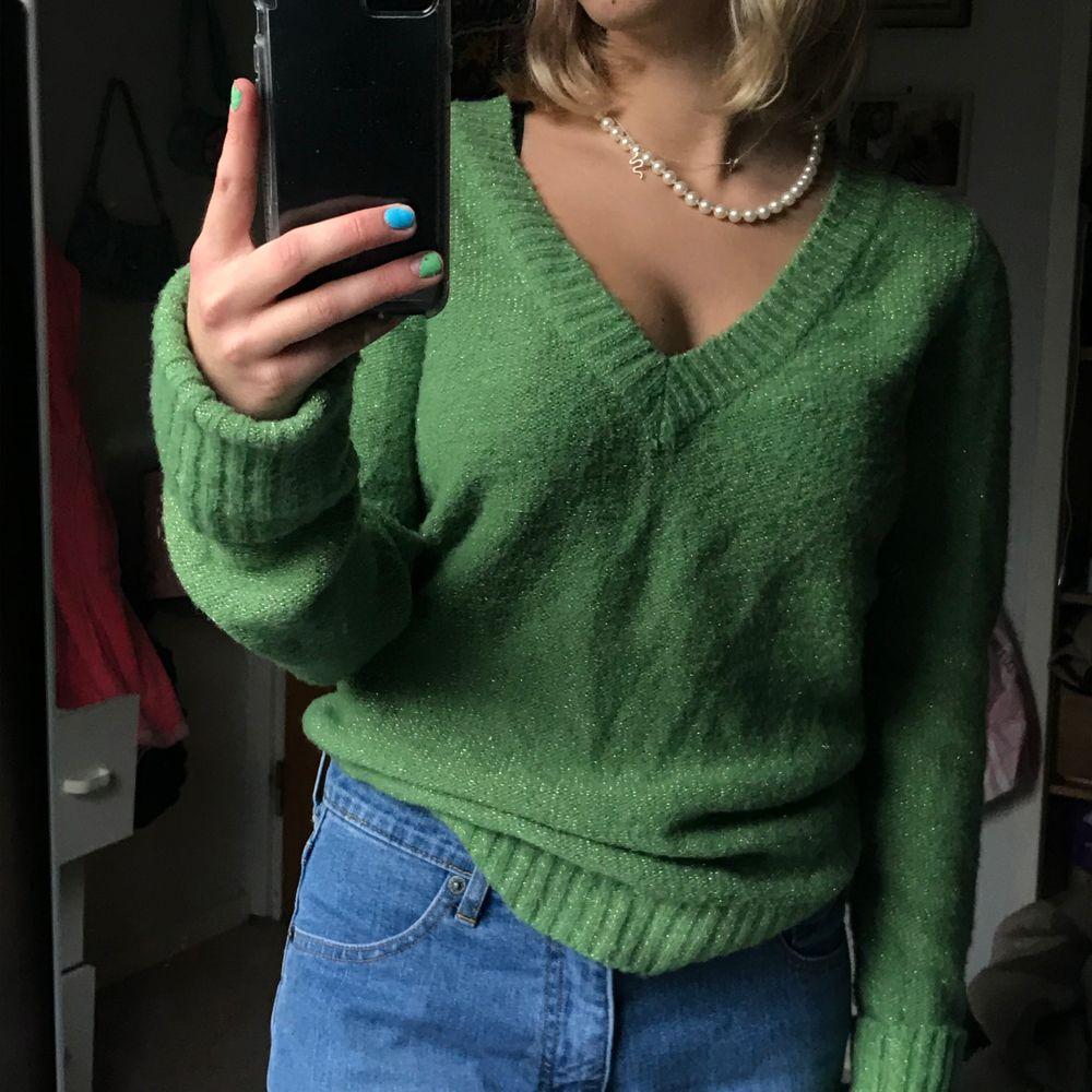 Grön stickad tröja med glitter. Den är köpt second hand och jag har använt den ungefär 1-2 gånger. Står L på lappen men tycker den sitter mer som S eller liten M beroende hur man vill den ska sitta. Vid stort intresse, buda i komentarerna. Stickat.