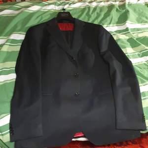 Kostym med kavaj och byxor. Svart i nyskick av märket Oscar Jacobson.