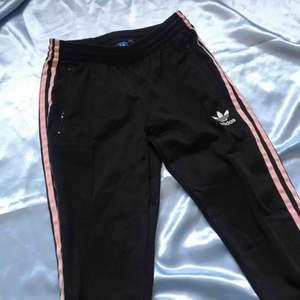 Svarta Adidasbyxor med rosa streck och raka, rätt smala ben. Blixtlås längst ner. Lite noppiga på ett ställe bak (se bild 3) men det går säkert att ta bort lätt 🌸