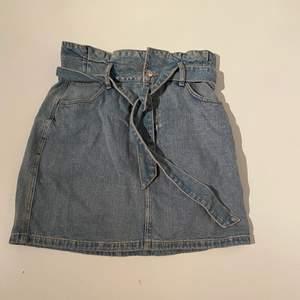Jeans kjol. Högmidja med knyt i midjan. Högmidja.