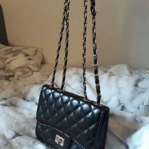Svart väska från ur och penn, man kan välja att ha den som en baguette väska t.e.x eller axelräms väska