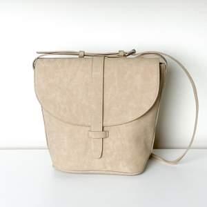 Beige väska som är lite större i botten och plattare upptill vid locket. Får plats med allt man behöver i den. Bra använt skick.