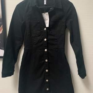 Svart långärmad jeansklänning från Zara. Aldrig använd, lappen kvar, storlek S. Nypris 399kr. Knäpps med knappar längs framsidan