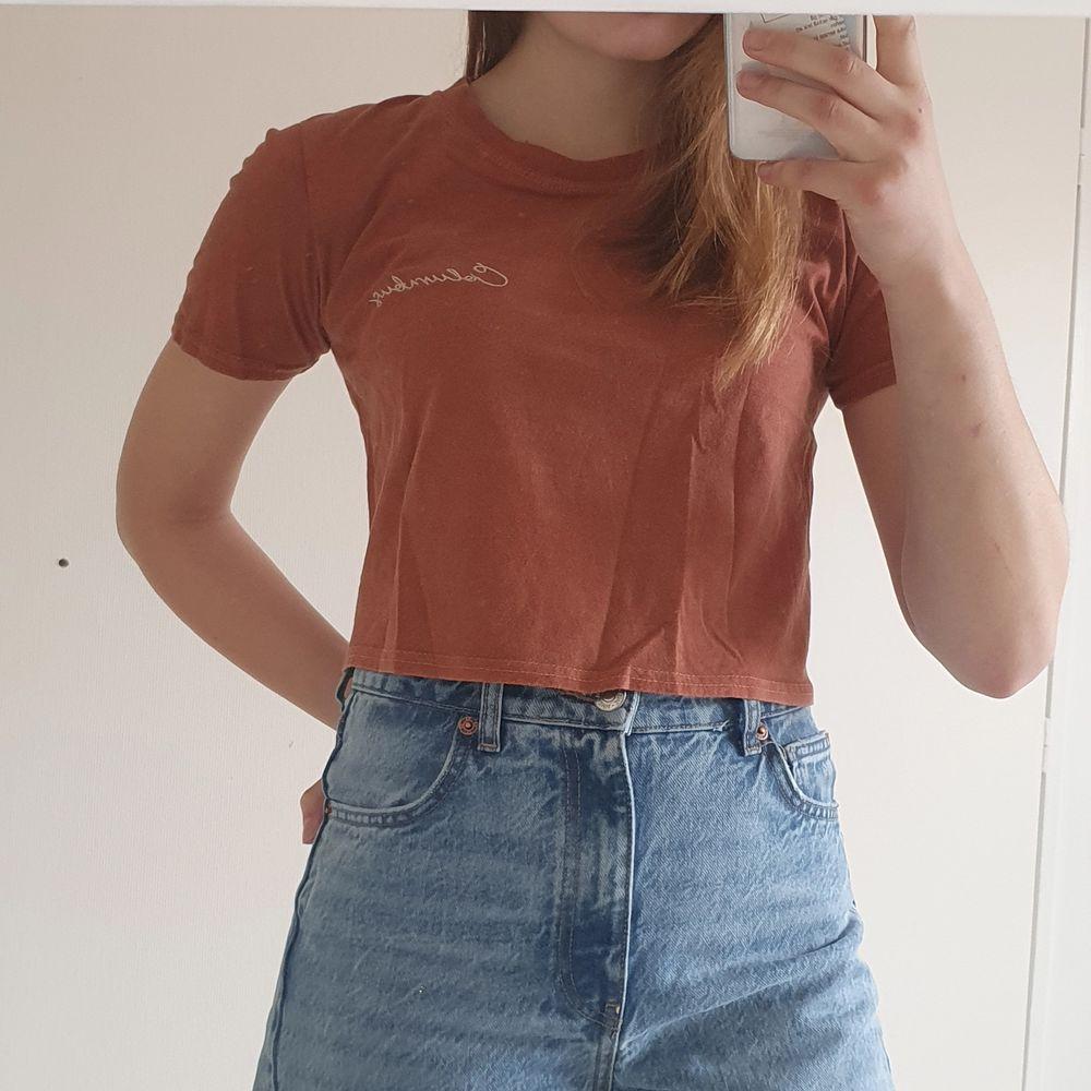 En t-shirt från Urban Outfitters, med ett tryck på ryggen och ett litet broderi I fram på bröstet. Första bilden visar alltså tröjans rygg. I mycket bra skick! Storlek S, passar även XS.. T-shirts.