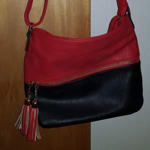 En jätte fin röd & svart crossbody väska som är lite använt. Jag säljer väskan eftersom att jag har bytt stil och använder därför inte den längre.