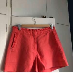 Korallrosa shorts med volanger i linne & bomull från j.crew. Färgen är mer rosa än orange. Väldigt fina till sommaren. Strl 0, passar XS-S. Fraktkostnad tillkommer. Budgivning från 50kr.