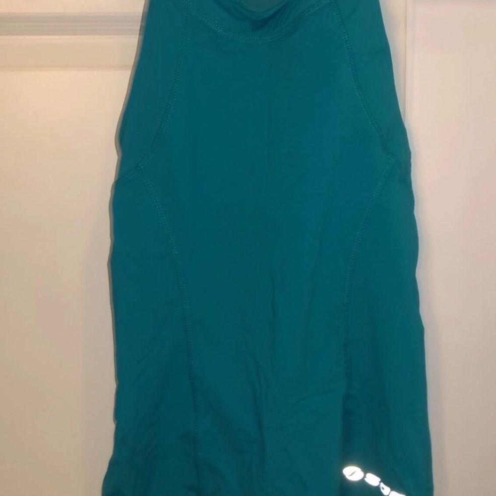 Blå tränings linne sitter tajt på kroppen, alldrig använt till träning om man inte räknar skolidrotten som träning. Huvtröjor & Träningströjor.