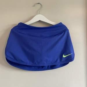 Lila tenniskjol med grönt Nike märke