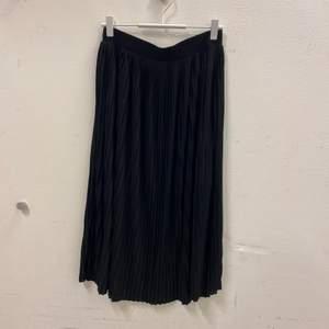 Plisserad svart midi-kjol. Supermjukt material och stretchig i midjan. Aldrig använd. Fler bilder kan tas vid önskemål. Frakt tillkommer