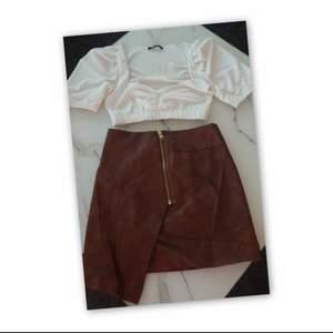 Skinnimitation kjol i brun färg, aldrig använd etiketten är fortfarande på.. köpt i HM 😍