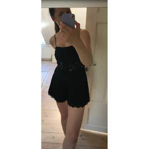 Jättesöt Jumpsuit / playsuit i svart med knäppning och spetskantade shorts nedtill samt spetsrand i midjan. Perfekt till sommaren, från Topshop (det står strl 36 i men den är ganska liten i storleken och är mer som en strl 34).