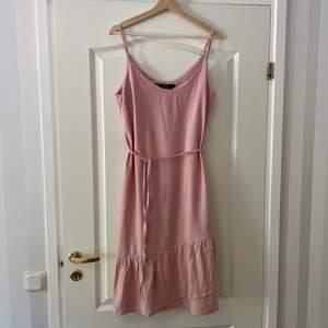 Askrosa klänning i vävd linneliknande kvalitet. Snörning i midjan och justerbara axelband. Volang detalj nertill. Använd 2-3 gånger. Köpt för ca 3 år sen.
