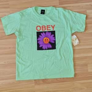 En snygg oanvänd t-shirt i storlek M från märket OBEY. Köpt på Carlings för 500kr, lappen sitter kvar. Säljer den för att den har bara legat i min garderob, den har inte kommit till användning och tycker att den borde få göra det. Pris går att diskuteras om man skriver till mig. FRAKT TILLKOMMER!