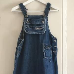 Jättefin jeansklänning! Fickan framtid kan plockas av om man vill. Axelbanden är reglerbara. Det går också att knyta ett band i ryggen för att reglera klänningens bredd. Klänningen når till mitten av smalbenen för mig som är 177cm. 60kr för frakt!