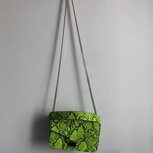 Neon grön o svart snake mönster. Med kedja och band. Från Zara. Super cool väska med två fickor. Finns bra utrymme för mobil och nycklar samt mer. Aldrig använt.
