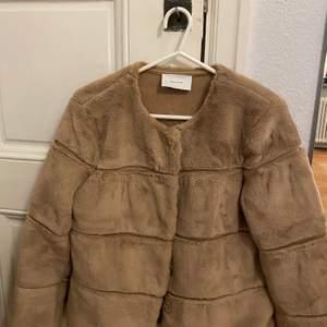 En jättefin beige fuskpälsjacka från Neo Noir i storlek small. Jackan känns som en riktig päls och är knappt använd.