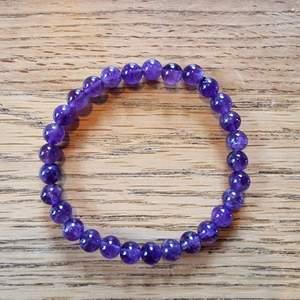 Armband med 6 mm stora kristallpärlor av ametist. Rundslipade stenar trädda på elastisk tråd. Ca 16 cm omkrets. Skickas i vadderat kuvert via postnord.