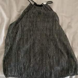 Gullig svart glittrig topp med öppen i ryggen! Oanvänd och prislapp kvar!