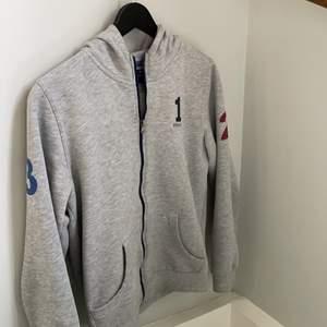 Skitsnygg grå hoodie med dragkedja från Hackett i storlek 13-14 (boys). Passar om du är runt 165cm lång✌🏽