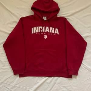en röd hoodie, i baggy form. små skador i form av smp håll vid hoodie fikan men inget man märker.  storlek M men skulle passa i L