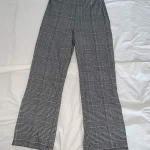 Ett par lättare vår/sommar byxor med svart-vit rutigt mönster. Med en full fungerande dragkedja på sidan av byxorna. Korta i modellen, går till anklarna!