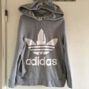 Ljusgrå Adidas huvtröja med tre-foil logo fram och stor genomgående ficka. Använd men i fint skick. Storlek 34-36, rymlig. UK 8