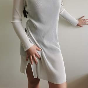 Vit genomskinlig klänning. Själv har jag på mig en tight klänning under, men du får såklart klä den som du vill!