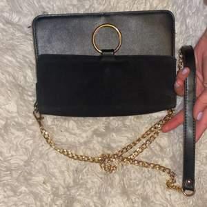 En svart axelväska med guldig kedja och svart rem! Stilren och snygg! Köpare står för frakt och skriv vid frågor!💕