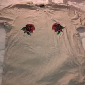 En ljusrosa t-shirt från ginatricot i storlek S med två roser!