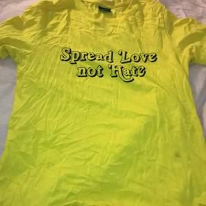 """En gul t-shirt med tryck på """"spread love not hate"""""""