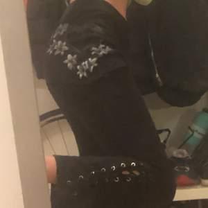 Ett par så snygga lite goth svarta byxor med insydd kjol och tryck på! De är utsvängda och lite lågmidjade! Jag är 175 cm lång🥰🥰😝😝
